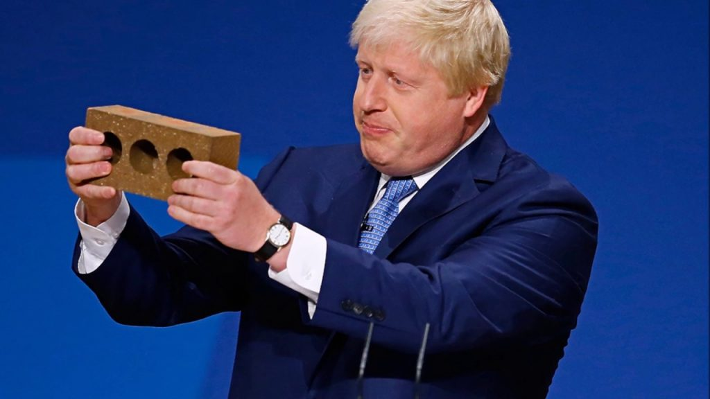 Boris holding a brick with 3 holes in it